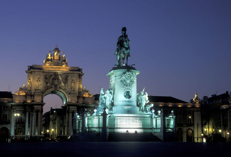 Statue At Praca Do Comercio Against Sky In City During Dusk