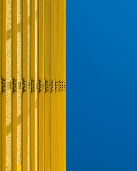 Close-up of yellow metal against blue sky
