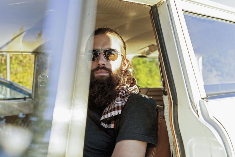 Bearded man sitting in a parked vintage car