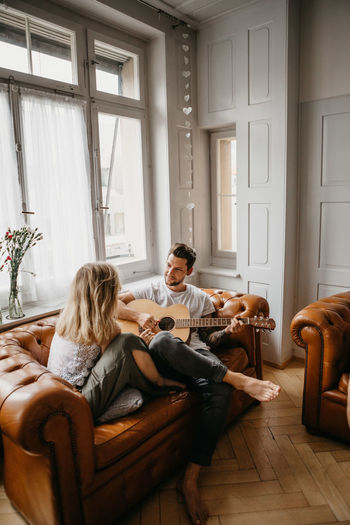 Man looking at woman while playing guitar on sofa