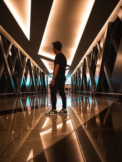 Rear view of man walking on illuminated bridge