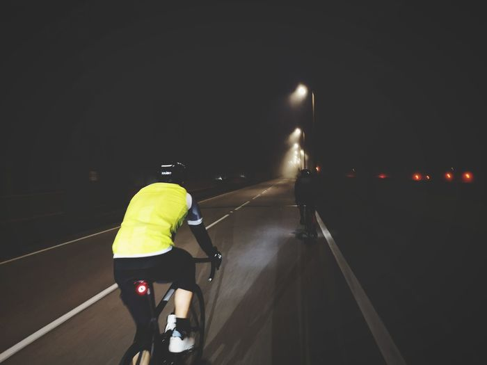 Rear view of man riding motorcycle on road at night