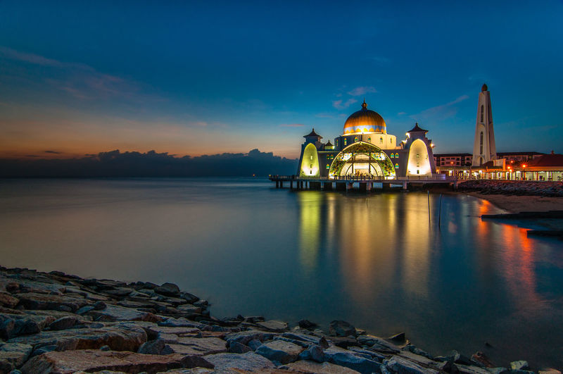Illuminated Mosque By Sea At Sunset