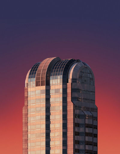 Low angle view of modern building against sky during sunset