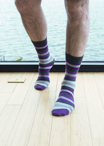 Mans legs showing him wearing striped socks standing by sea view window vertical portrait. Adult Bare Dating Relationship Adult Affair Cheating Close-up Day Feet Hairy  Human Body Part Human Leg Indoors  Legs Low Section Male Masculine Morning After One Person People Purple Real People Socks Striped