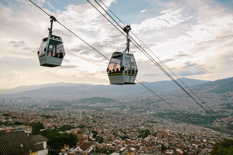 Overhead cable car in city against sky