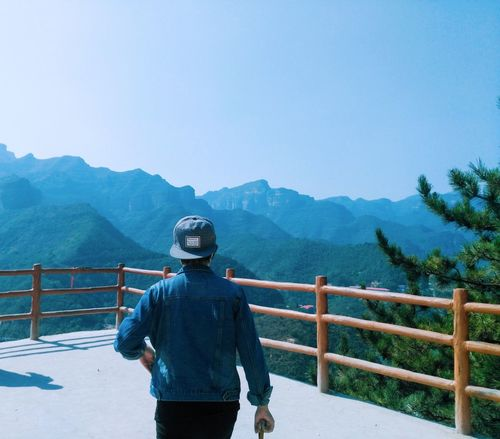 Mountain Railing Rear View Scenics Mountain Range Tranquil Scene Blue Tranquility Clear Sky Idyllic Beauty In Nature Standing Leisure Activity Men Majestic Casual Clothing Non-urban Scene Water Solitude Remote
