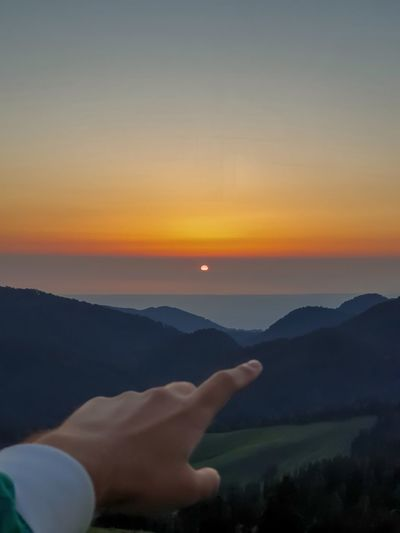 Midsection of woman against mountains during sunset