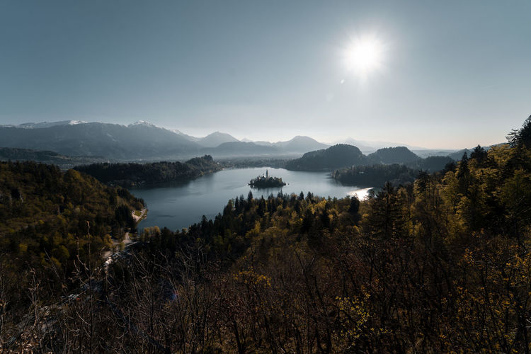 After sunrise in Bled, Slovenia Sky Mountain Beauty In Nature Water No People Sun Scenics - Nature Tranquility Nature Tranquil Scene Non-urban Scene Environment Plant Sunlight Mountain Range Lake Idyllic Outdoors Tree Lens Flare Bright