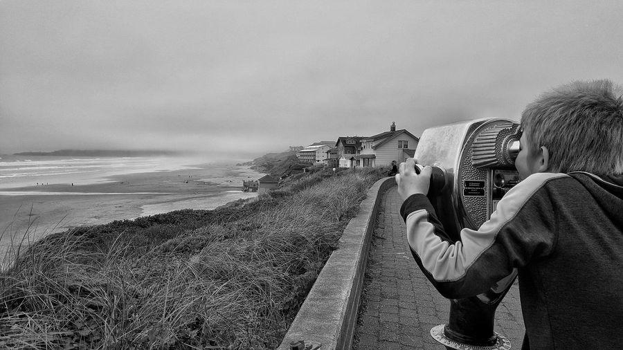 Rear view of boy looking through coin-operated binoculars on promenade against cloudy sky