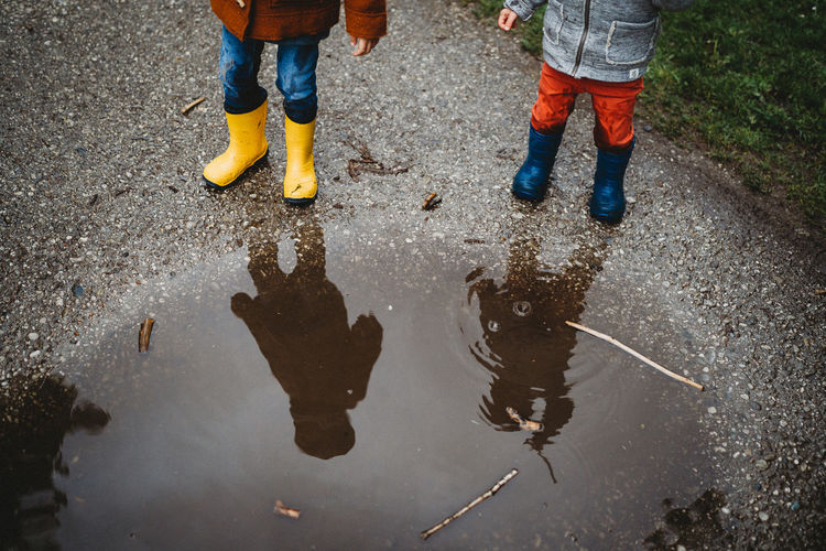 Low section of men with reflection on puddle