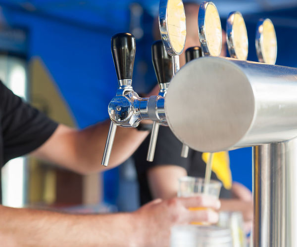 Barman hand at beer tap pouring a draught lager beer serving in a restaurant or pub. Beer Drought Pub Bar Brewing Close-up Draft Draught Drink Faucet Focus On Foreground Human Hand One Person Tap Working