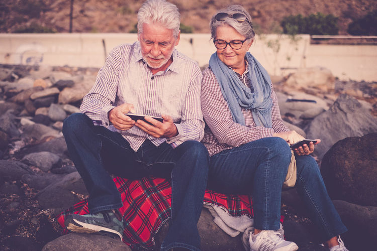 senior couple white and grey hair, mobile technology, front of ocean Adult Bonding Casual Clothing Communication Curiosity Day Eyeglasses  Happiness Holding Lifestyles Outdoors People Real People Retirement Rock Beach Senior Adult Senior Couple Sitting Smiling Technology Togetherness Two People Wireless Technology