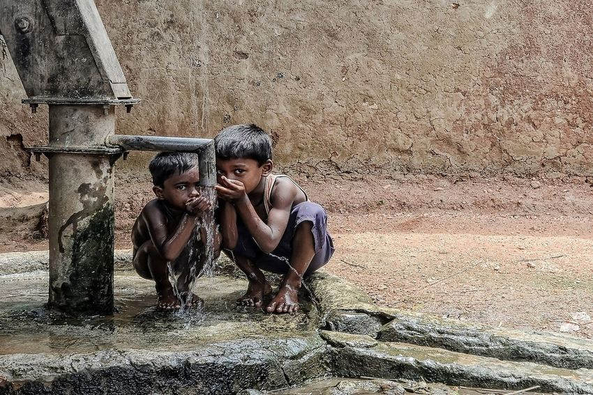 Parched - Two kids share their thirst for water. Taken in a rural village in West Bengal. During the days of summer, the soil gets parched and dry. Many areas face severe water crisis. The local municipality and village administration tries to bring relief through these tube wells. On World Water Day lets take a pledge not to waste a single drop Bengal Debarshi Mukherjee Photography India Rural Travel Child Childhood Day Debarshimukherjee Documentary Friendship People Portrait Summer Two People Village Water Worldwaterday EyeEmNewHere Summer Exploratorium Summer Exploratorium Focus On The Story #FREIHEITBERLIN The Street Photographer - 2018 EyeEm Awards