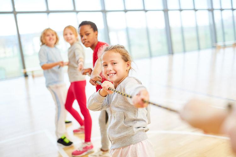 Students playing tug-of-war at school gymnasium
