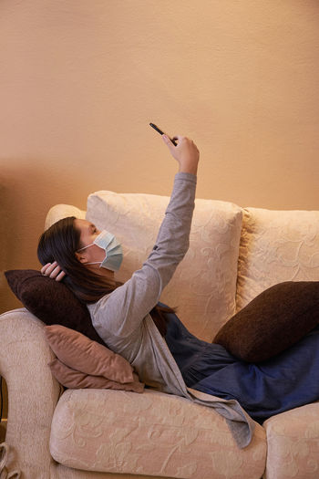 Midsection of woman using mobile phone on sofa