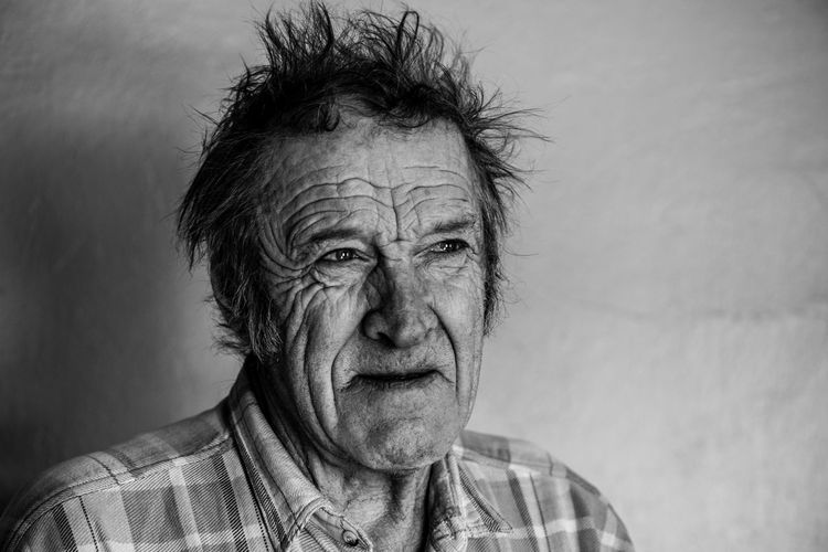 Close-Up Of Serious Senior Man Looking Away Against Wall