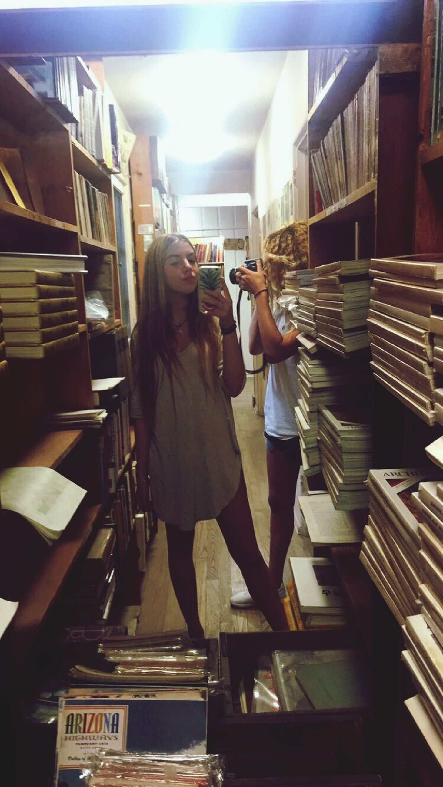 two people, young adult, young women, adults only, choosing, shelf, full length, togetherness, choice, people, only women, women, indoors, adult, standing, females, large group of objects, bonding, variation, education, real people, day
