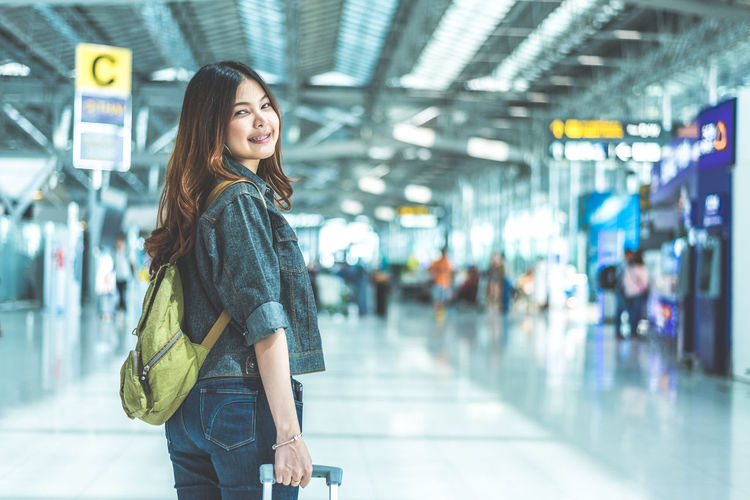 Full length of smiling woman standing at airport