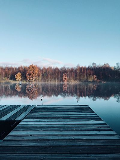 Pier over lake against trees during autumn