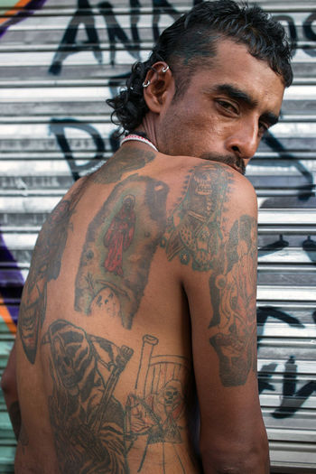 a devotee during the mass for the cult of the Santa Muerte, held in a street in Tepito on the first of every month in Mexico City. Close-up Cult Devotee Gang Lifestyles Man Outdoors Portrait Religion Santa Muerte Scary Tattoo The Street Photographer - 2016 EyeEm Awards Tough First Eyeem Photo