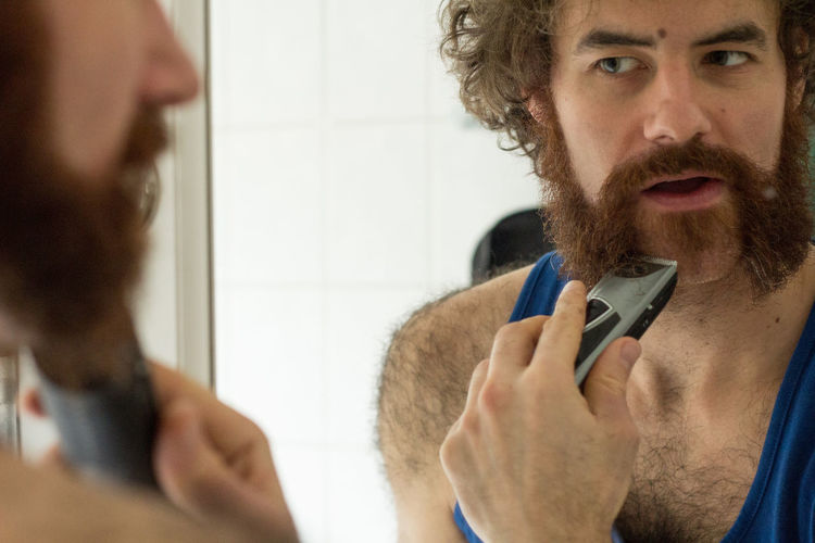Reflection of man trimming beard on bathroom mirror