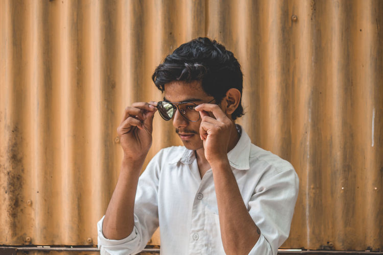 Teenage boy wearing broken sunglasses looking away against corrugated iron