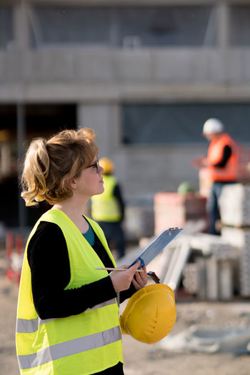 Female engineer holding hardhat and clipboard at construction site