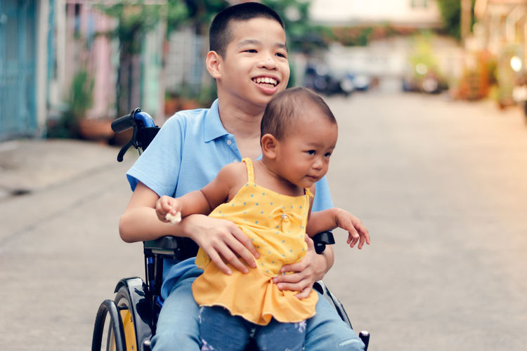 Disable boy holding cute sister while sitting on wheelchair