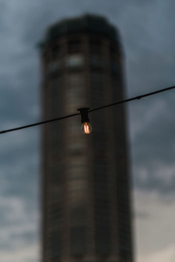 A light for a city Electricity  Lighting Equipment Cable Built Structure Building Exterior Silhouette Animal Wildlife Bird Architecture Animal Outdoors Vertebrate Cloud - Sky Animal Themes Dusk Low Angle View No People Animals In The Wild One Animal Nature Sky Selective Focus Illuminated Electricity