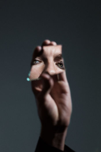 Cropped hand holding mirror with reflection of woman eyes against gray background