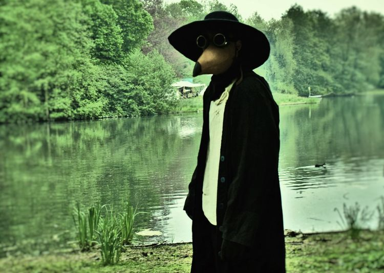 Plague doctor Beauty In Nature Clothing Day Fashion Hat Lake Leisure Activity Lifestyles Middle Ages Mystery Nature One Person Outdoors Plague Doctor Plant Real People Side View Standing Three Quarter Length Tranquility Tree Water Young Adult
