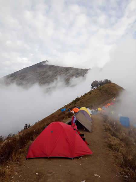 Trekkers camp on Mount Rinjani. Most will attempt to reach the summit by sunrise the next morning. INDONESIA Red Wanderlust Adventure Beauty In Nature Camping Cloud - Sky Cold Temperature Day Dramatic Landscape Environment Fog Land Landscape Mountain Mountain Peak Nature Non-urban Scene Outdoors Rinjani Scenics - Nature Sky Tent Tranquil Scene Travel Destinations