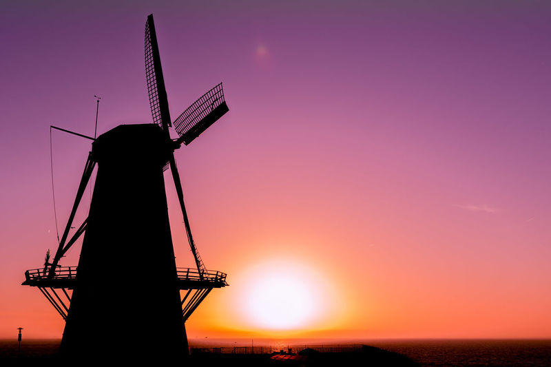 Silhouette windmill on field against sky during sunset