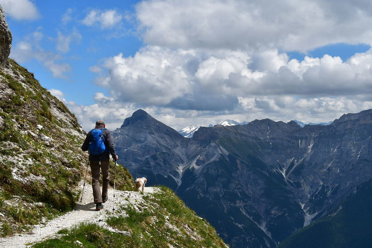 Rear view of man with dog standing on mountain against sky