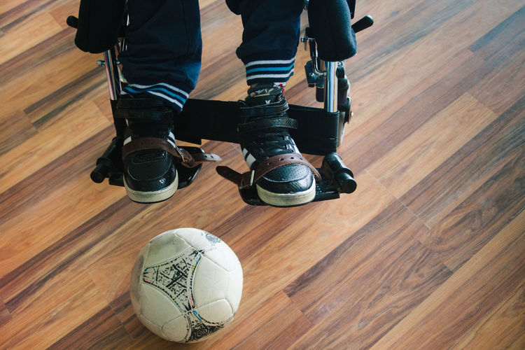 Low section of person sitting on wheelchair by soccer ball at home
