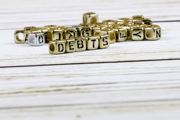 Close-up of debt text made with golden toy blocks on table