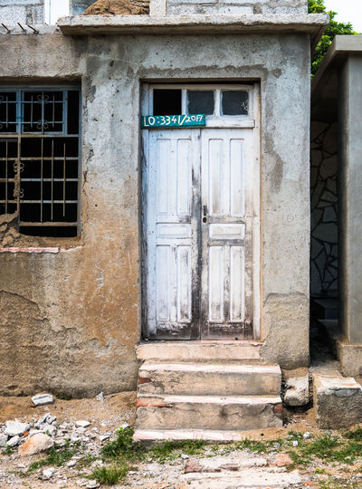 Las Tunas, Cuba - September 2017: Front door of a rundown house in Cuba. 3rd World Cuba Life Living Travel Weathered Architecture Building Exterior Built Structure Colorful Door Embargo Exterior Historic No People Outdoors Poverty Street Third World Country Tropical Climate Worn Worn Down EyeEmNewHere