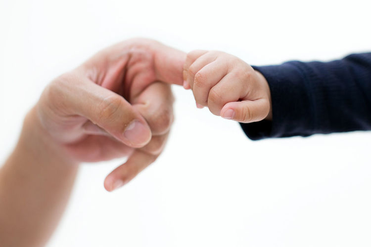 Close-up of man holding hands over white background