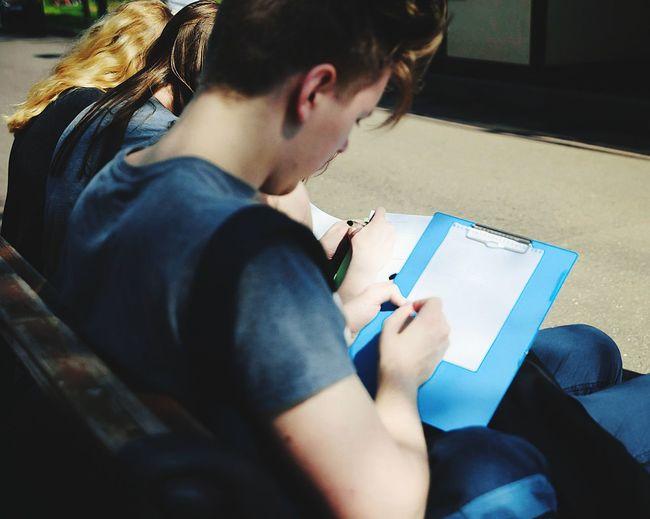 Man writing while sitting on bench