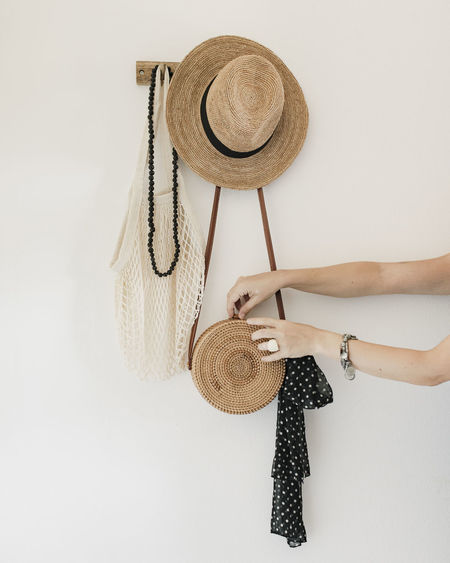 Midsection of woman holding hat against white background