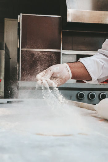 Cropped hand of chef preparing food in commercial kitchen