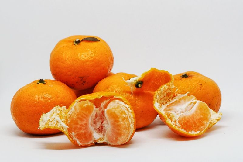 Ripe tangerines with green leaves and peaked segments isolated on white background Blood Orange Citrus Fruit Close-up Day Food Food And Drink Freshness Fruit Healthy Eating No People Orange - Fruit Orange Color Studio Shot White Background