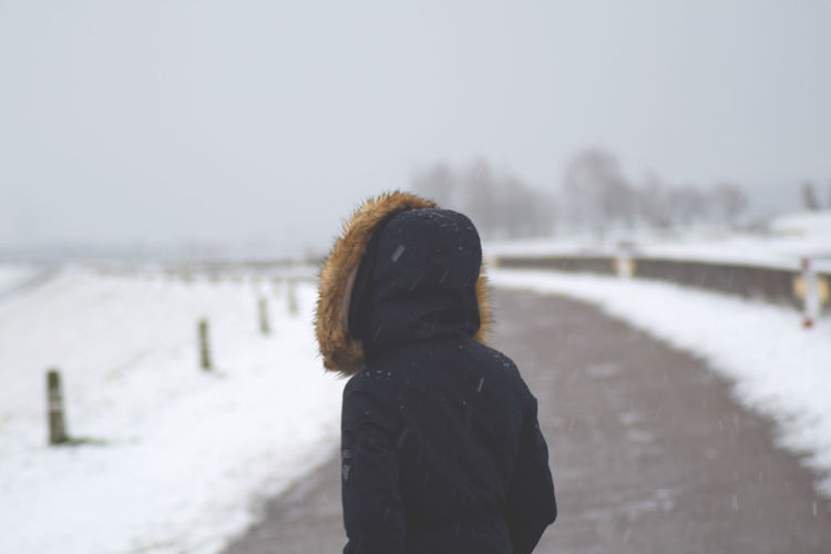 Woman standing on road during snowfall