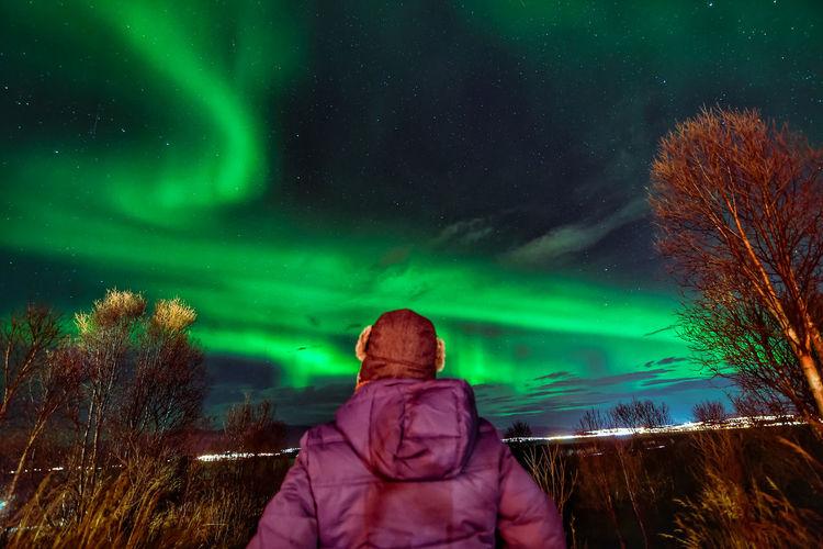 Rear view of mature man looking at aurora borealis in sky at night