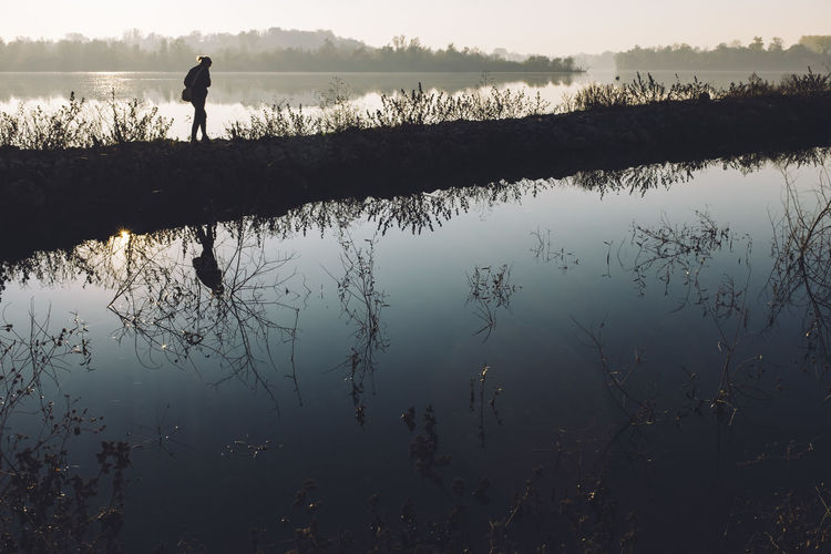 Silhouette Woman Walking By Water Against Countryside