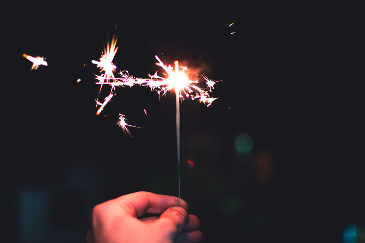 Cropped hand holding lit sparkler at night