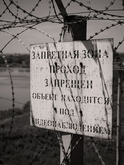 запретная зона Water Communication Barbed Wire Text Safety Protection Warning Sign Close-up Sky Warning High Voltage Sign Razor Wire