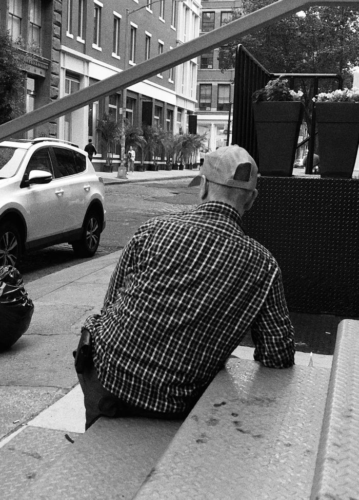 REAR VIEW OF MAN ON STREET AGAINST CITY
