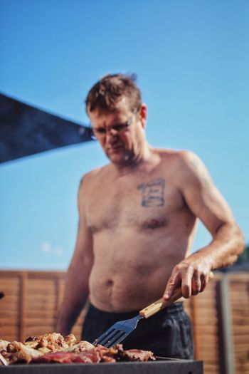 Shirtless man grilling food outdoors